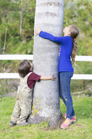 girl in the forest: Portrait of Happy Children Hugging a Tree