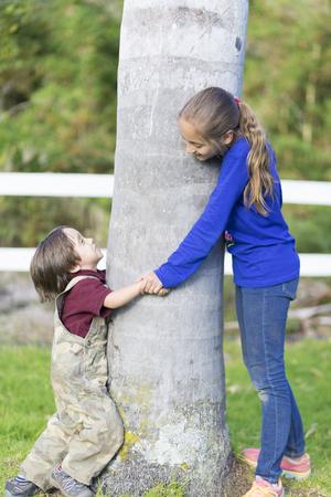 jungle girl: Portrait of Happy Children Hugging a Tree