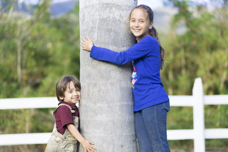 cute girl: Portrait of Happy Children Hugging a Tree