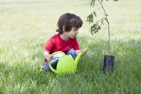 watering plants: Portrait of Lovely Boy Watering Plants Outdoors