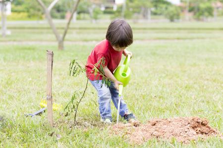 regar las plantas: Niño pequeño regar las plantas al exterior