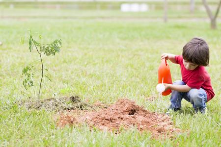 regar las plantas: Retrato de hermosas plantas de riego del muchacho al aire libre Foto de archivo