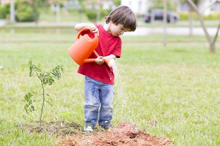 Retrato de hermosas plantas de riego del muchacho al aire libre