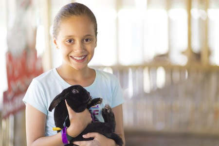 Happy Girl Playing with Rabbit in the Farm photo