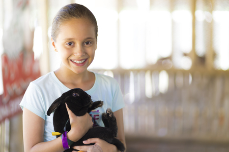 Happy Girl Playing with Rabbit in the Farm