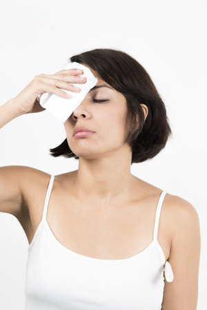 Portrait of a sick woman blowing her nose