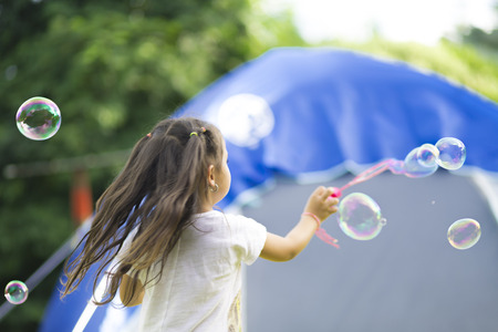 Happy Girl Playing with Soap Bubbles Stock Photo