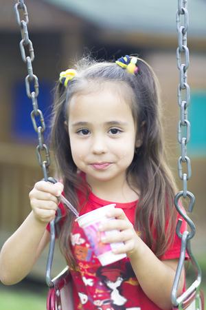 Happy girl drinking milk or yogurt in the park