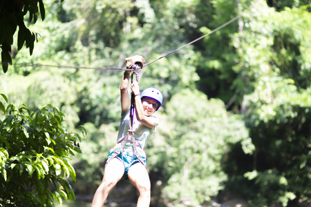 Happy Girl  in-motion on zipline in tropical jungle rainforest Tree Canopy