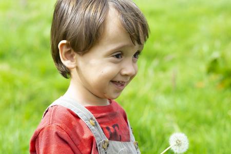 Happy boy blowing white dandelion outdoors