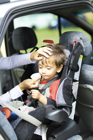 Happy Mother helping her son to fasten, seatbelts in the car