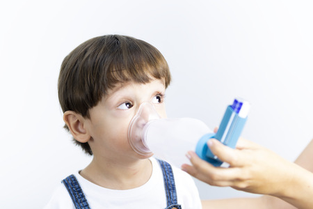 Young boy using inhaler for asthma and respiratory diseases Stockfoto