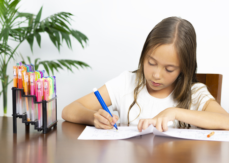 Children Education Concept, Cute Girl Sitting at his Desk Painting