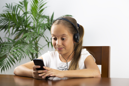 Smiling Girl Relaxing, Playing Music Using Smartphone and Wearing Headphones at Home