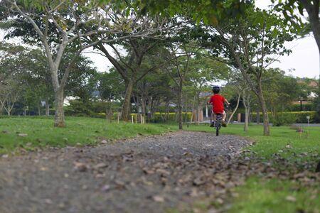 Cheerful Little Boy Riding a Bike in the Park Reklamní fotografie