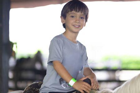 Happy Boy Riding a Horse in a Ranch Фото со стока