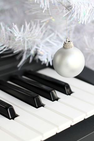 Image of a piano with shiny Christmas decoration ball hanging from a string Stock Photo