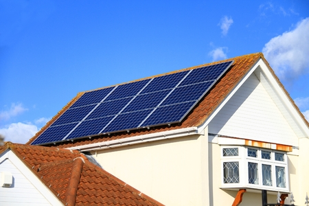 Solar panel on top of a roof with blue sky in the background on a sunny day