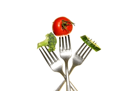 Image of fresh vegetables on a fork with white background taken in a photography studio