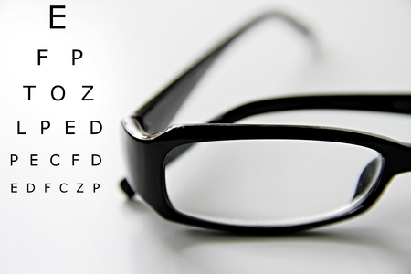 close up with glasses with reading text chart Stock Photo