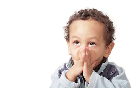 little boy praying with hands together on white background stock photo