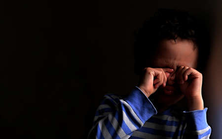 poor boy in poverty with no help alone and all by himself stock photo