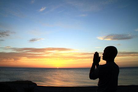 man praying to god with hands together Caribbean man praying stock image stock photo