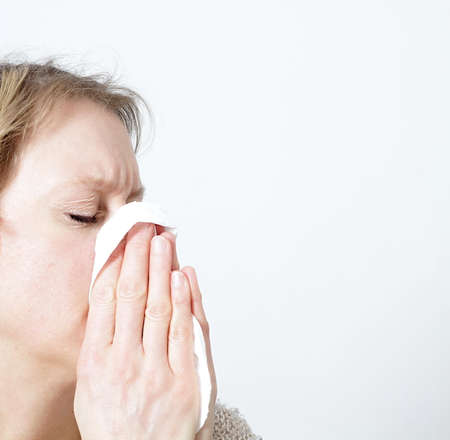 woman with allergy blowing her nose in a handkerchief stock image and stock photo