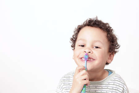 little boy brushing his teeth with an electric tooth brush stock image with white background stock photo