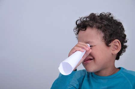 boy looking through white paper on grey background stock photo Reklamní fotografie