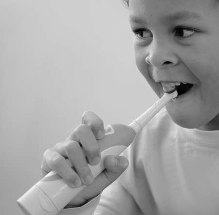 little boy brushing his teeth with an electric tooth brush with grey background stock photo