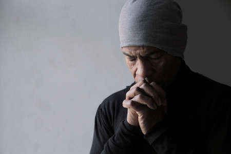 man praying to god with hands together Caribbean man praying with grey background stock photo