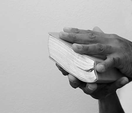 praying to god with hands on bible at church stock photo