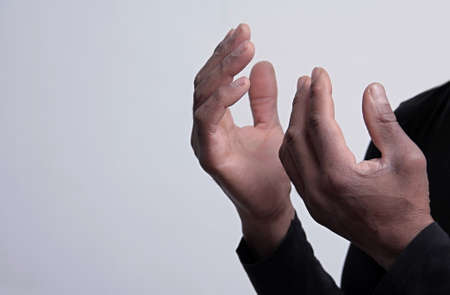 man praying to god with hands together on black background stock photo
