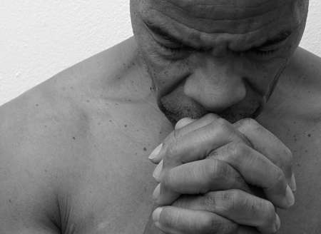 man praying to god with hands together Caribbean man praying with white background stock photo