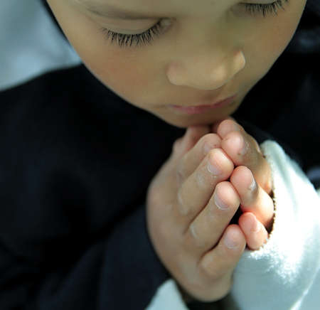 boy praying to God with hands together stock photo