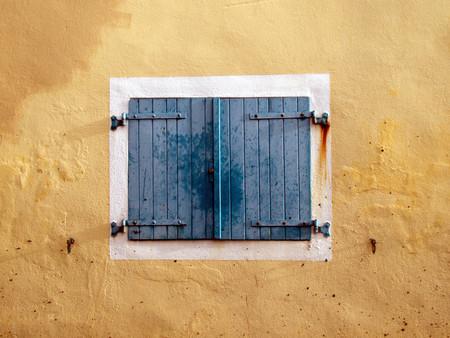 ocher wall and wooden shutters.