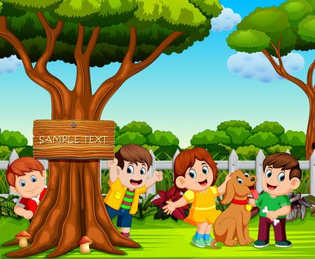 los niños felices están jugando cerca del gran árbol.