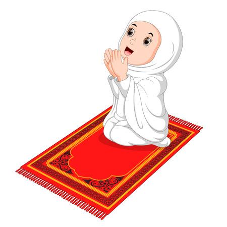 Ragazza musulmana seduta sul tappeto da preghiera mentre prega
