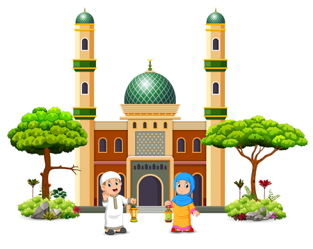 the boy and the girl are holding the ramadan lantern in front of the green mosque Stock Photo
