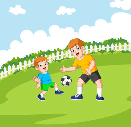 The two boys are playing the football the green field