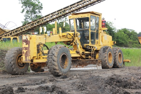 grader: Grader in the coal mine site which still operate Stock Photo