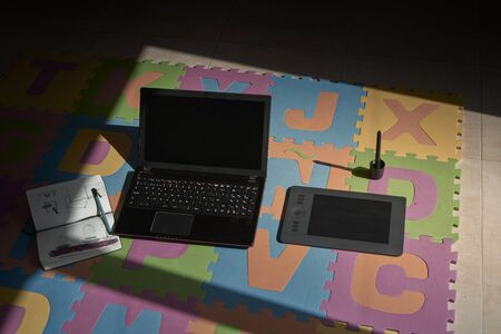 Top view of laptop with graphics tablet on a carpet with colored letters. I work at home Foto de archivo