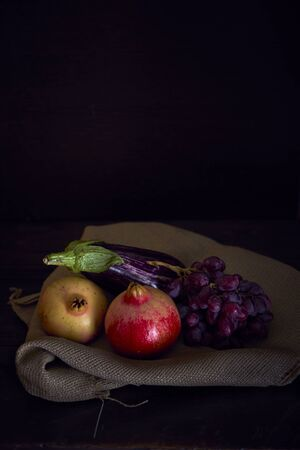 vertical still life of eggplant and pomegranate with grape on sackcloth dark lighting