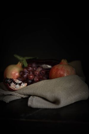 vertical eggplant and pomegranate still life with grape on sackcloth dark lighting