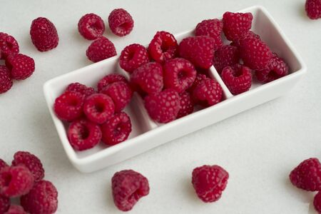 Closeup of raspberries in a white bowl on white background, Copy space
