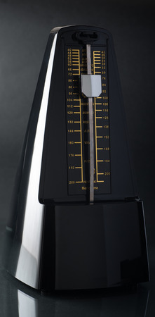 metronome: Close up of a metronome on black background