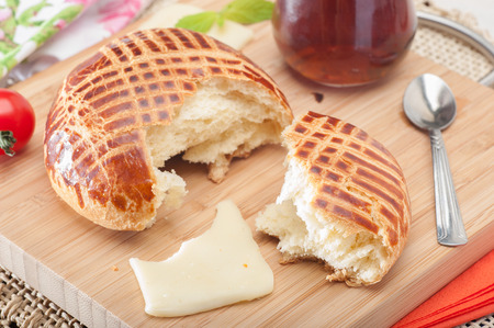 Close up of a half typical Turkish owen product pastry pogaca on wood plate with cheese tomato and tea Stok Fotoğraf