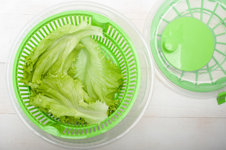 Close up of salad spinner with lettuce on white table 写真素材