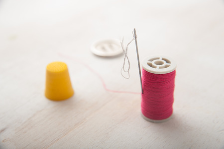 alterations: Macro shot of thread and needle on white wooden background Stock Photo